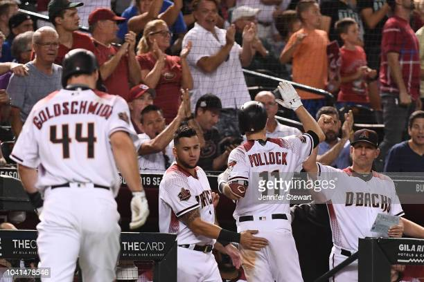 J Pollock of the Arizona Diamondbacks is congratulated by David Peralta and manager Torey Lovullo after hitting three run home run in the fifth...