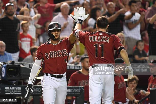 J Pollock of the Arizona Diamondbacks is congratulated by Ketel Marte after scoring against the Houston Astros in the sixth inning of the MLB game at...