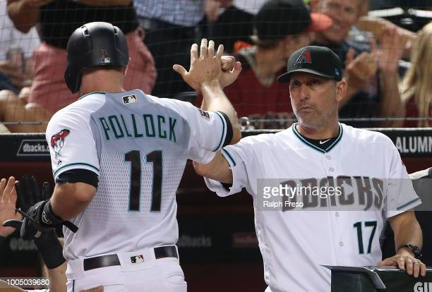 J Pollock of the Arizona Diamondbacks is congratulated by manager Torey Lovullo after scoring a run against the Colorado Rockies during the fifth...
