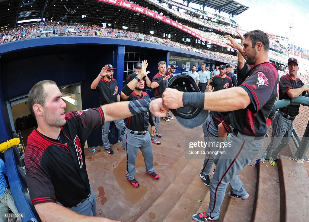 A. J. Pollock #11 of the Arizona Diamondbacks is congratulated by Paul Goldschmidt #44 after scoring a first inning run against the Atlanta Braves at SunTrust Park on July 15, 2017 in Atlanta, Georgia.