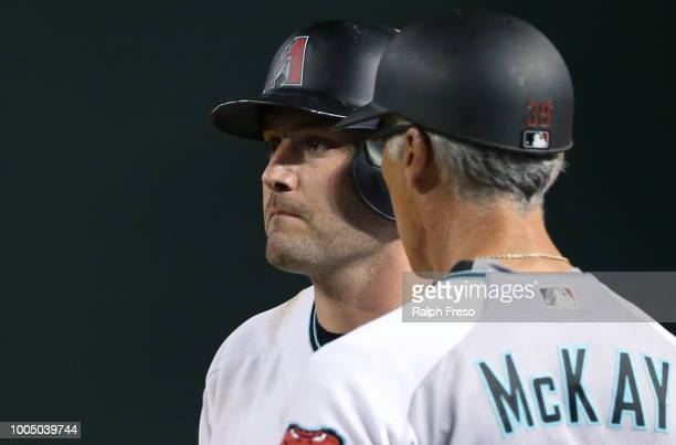 J Pollock of the Arizona Diamondbacks looks on next to first base coach Dave McKay after hitting a single against the Colorado Rockies during the...