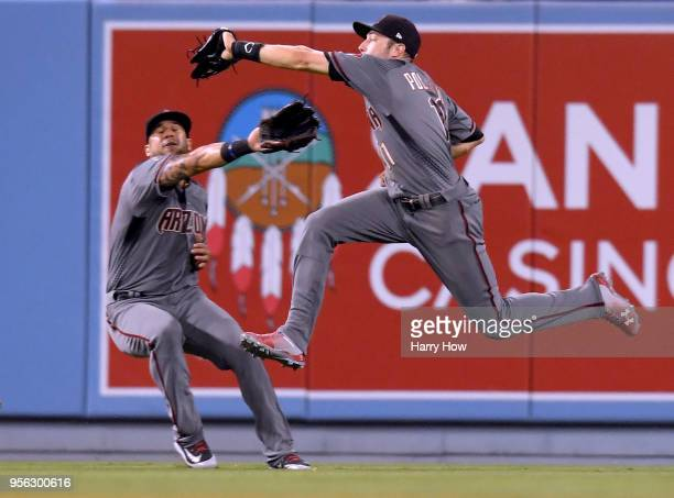 J Pollock of the Arizona Diamondbacks makes a running catch in front of David Peralta for an out of Chris Taylor of the Los Angeles Dodgers to end...