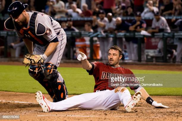 J Pollock of the Arizona Diamondbacks points to the third base umpire to confirm an interference call against Alex Bregman of the Houston Astros in...