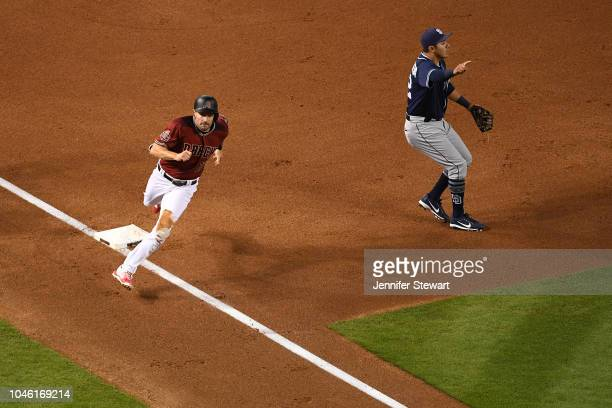 J Pollock of the Arizona Diamondbacks rounds third base in front of Christian Villanueva of the San Diego Padres during the MLB game at Chase Field...