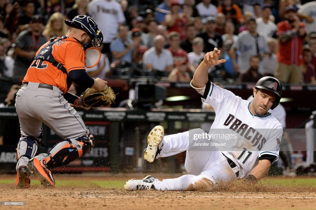 A.J. Pollock #11 of the Arizona Diamondbacks safely slides home to score in front of Max Stassi #12 of the Houston Astros in the fifth inning at Chase Field on August 15, 2017 in Phoenix, Arizona.