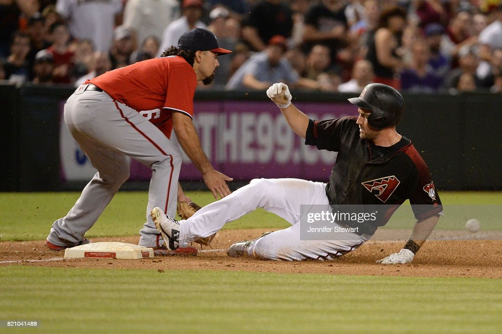 A.J. Pollock #11 of the Arizona Diamondbacks safely slides in front of Anthony Rendon #6 of the Washington Nationals for a triple during the sixth inning of the MLB game at Chase Field on July 22, 2017 in Phoenix, Arizona.