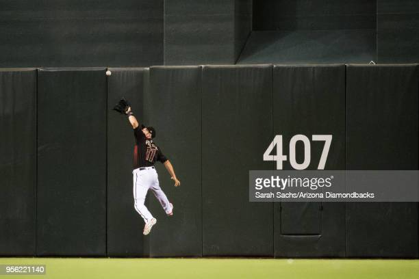 J Pollock of the Arizona Diamondbacks scales the wall to catch a fly ball during a game against the Houston Astros at Chase Field on May 5 2018 in...