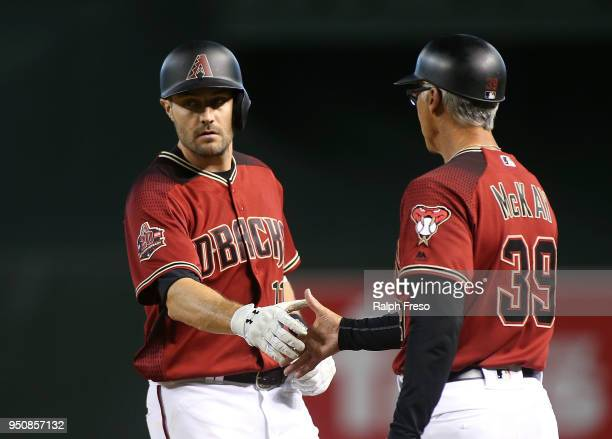 J Pollock of the Arizona Diamondbacks slaps hands with first base coach Dave McKay after hitting a single against the San Diego Padres during the...