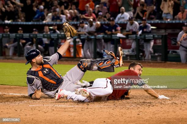 J Pollock of the Arizona Diamondbacks slides into home plate against Brian McCann of the Houston Astros to score on an interference error against...