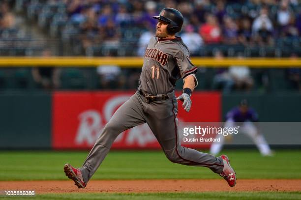 J Pollock of the Arizona Diamondbacks starts to slide into third base with a first inning triple against the Colorado Rockies at Coors Field on...