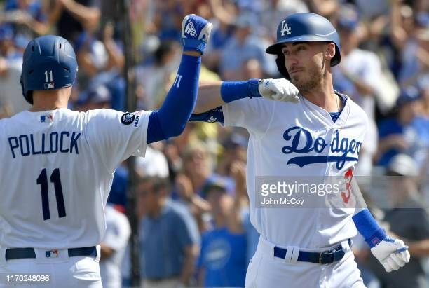 J Pollock of the Los Angeles Dodgers congratulates Cody Bellinger for his grand slam home run against the Colorado Rockies in the fifth inning at...