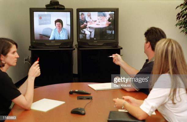 Polycom employees Lesley Philips Kimberly Klawuhn and Victor Goodrun talk to fellow employee Alicia Morehouse October 3 2001 on a video conferencing...