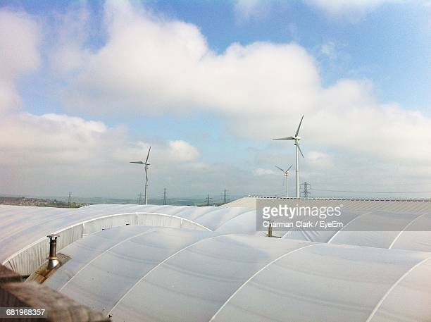 Polyethylene Tunnel By Wind Turbine Against Sky