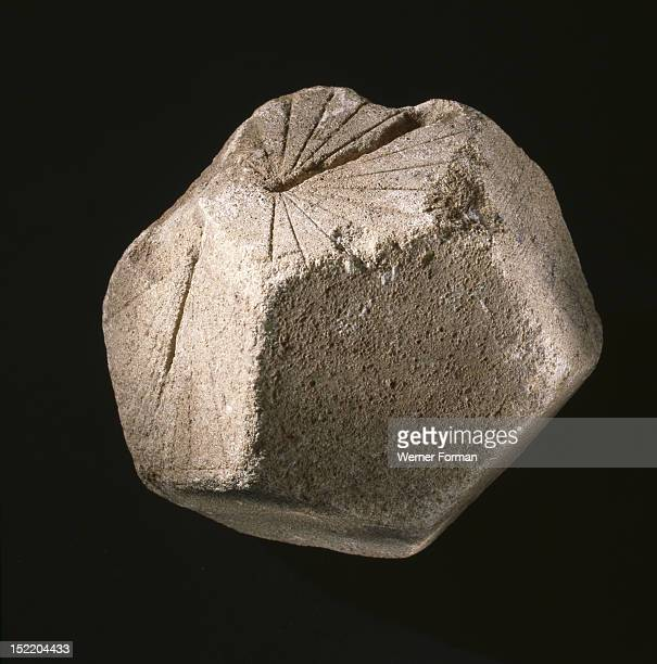 A polyhedral block dial of unknown origin the block is a pentagon dodecahedron with sundial incisions on three faces
