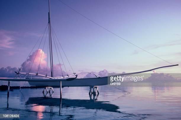 Catamaran dans de l'eau de lagon polynésien au coucher du soleil