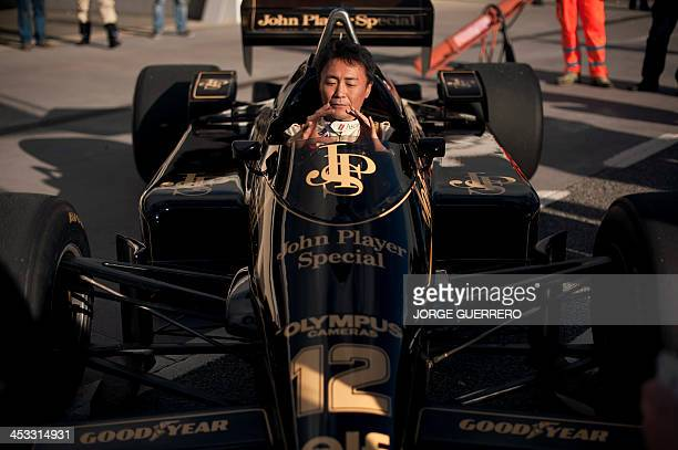 Polyphony Digital Inc president and creator of the series best selling PlayStation Gran Turismo Japanese Kazunori Yamauchi gestures inside a lotus...