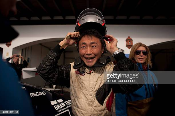 Polyphony Digital Inc president and creator of the series best selling PlayStation Gran Turismo Japanese Kazunori Yamauchi reacts as he puts a helmet...