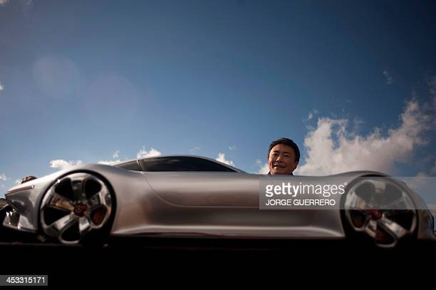 Polyphony Digital Inc president and creator of the series best selling PlayStation Gran Turismo Japanese Kazunori Yamauchi poses behind a model car...