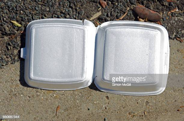 polystyrene takeout burger container littering a road gutter - polystyrene stock pictures, royalty-free photos & images