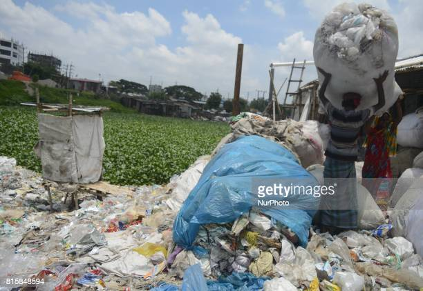 Polythene recycling worker during work besides Buriganga river on July 16 2017 in Dhaka Bangladesh Buriganga river which flows by Dhaka now one of...