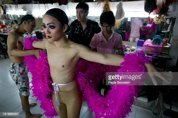 Pom a ladyboy dancer at the Chiang Mai Cabaret show gets fitted with a new costume backstage before a performance September 8 2012 in Chiang Mai...
