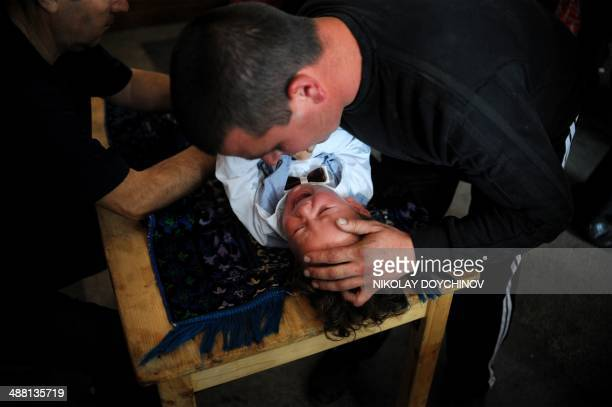 A Pomak man comforts his child while a doctor injects an anesthetic prior to performing circumcision during a mass circumcision ceremony for young...