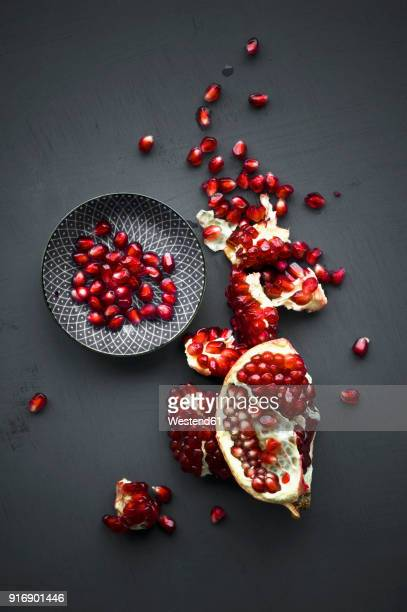 pomegranate and pomegranate seeds in bowl - tropische frucht stock-fotos und bilder