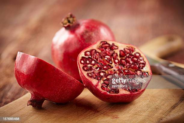 pomegranate fruit on cut board - pomegranate stock pictures, royalty-free photos & images