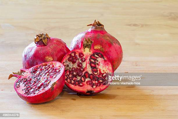 Pomegranate fruit opened in half real life imperfect fruit over a cutting board in a house kitchen during daytime and with natural light