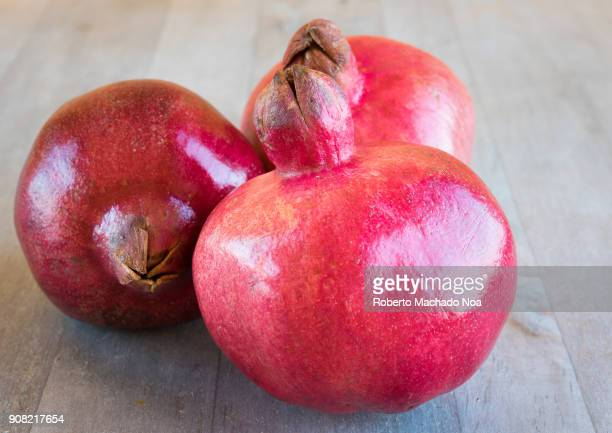 Pomegranate fruits over a wooden surface The healthy food is rich in antioxidants and vitamin C
