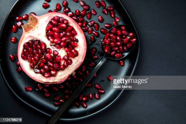 pomegranate half on plate - pomegranate stock pictures, royalty-free photos & images