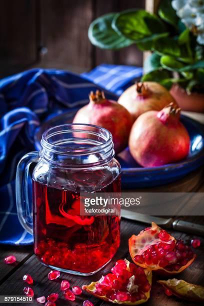 Vidrio del jugo de Granada sobre la rústica mesa de madera