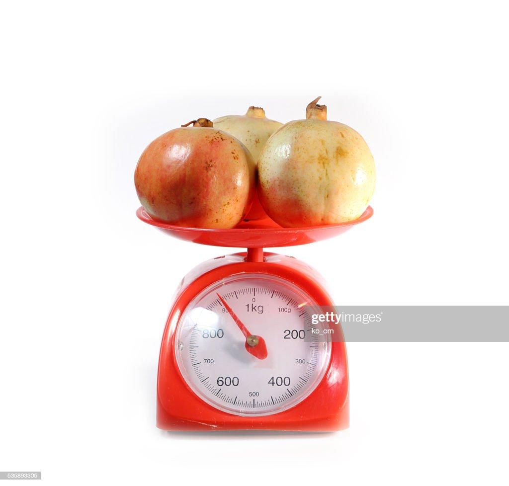 pomegranate on red weighing scale : Bildbanksbilder
