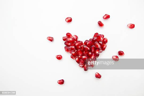 pomegranate seed heart - pomegranate stock pictures, royalty-free photos & images