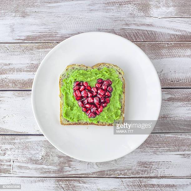 Pomegranate seeds and smashed avocado on seeds toast.