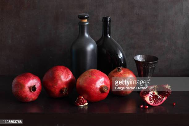 pomegranates and black bottles - still life stock pictures, royalty-free photos & images