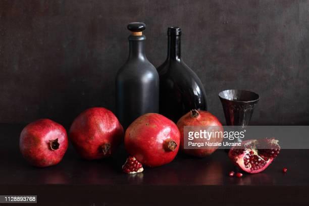 pomegranates and black bottles - stilleven stockfoto's en -beelden