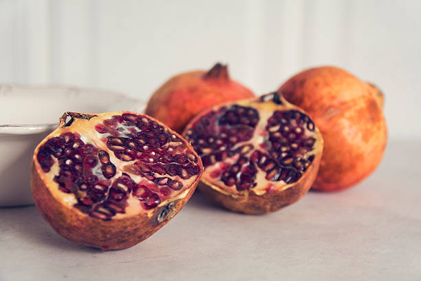 pomegranates halved on a table - pomegranate tree stock photos and pictures
