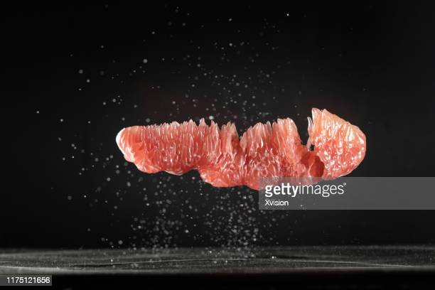 pomelo peeled flying in mid air captured with high speed - grapefruit red stock pictures, royalty-free photos & images