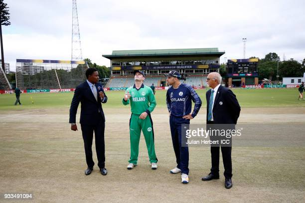 Pommie Mbangwa and Match Referee Dev Govindjee oversee the Coin toss by William Porterfield of Ireland and Matthew Cross of Scotland during The ICC...