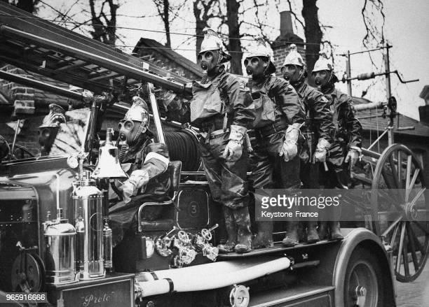 Pompiers de la 'Air Raid Precautions' vêtus de combinaisons de protection et portant un masque à gaz sur le camion défilent dans les rues de Londres...