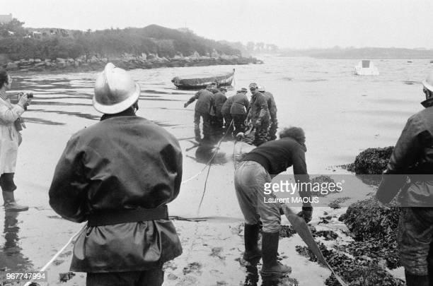 Pompiers et bénévoles lors du nettoyage de la plage après le naufrage du pétrolier Amoco Cadiz le 21 mars 1978 à Portsall France