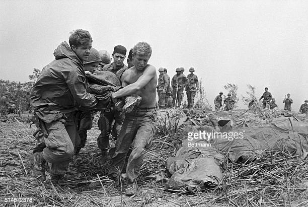 Ponchocovered bodies of American soldiers killed in action lie on a hill near Khe Sanh as troops carry the bodies of the dead to waiting evacuation...