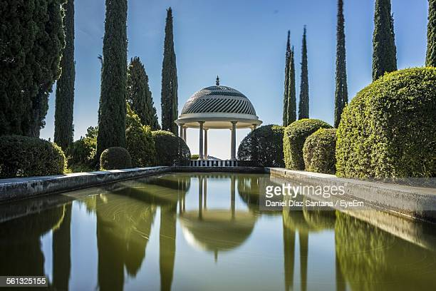 pond and gazebo amidst trees against clear sky in park at fuengirola - fuengirola stock photos and pictures