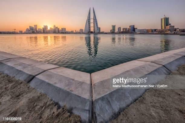 pond in city against sky at sunset - bahrain stock pictures, royalty-free photos & images