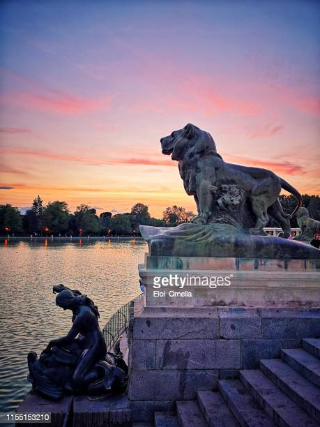 pond of buen retiro park at sunset, madrid. with a view of the different statues of the area - madrid stock pictures, royalty-free photos & images