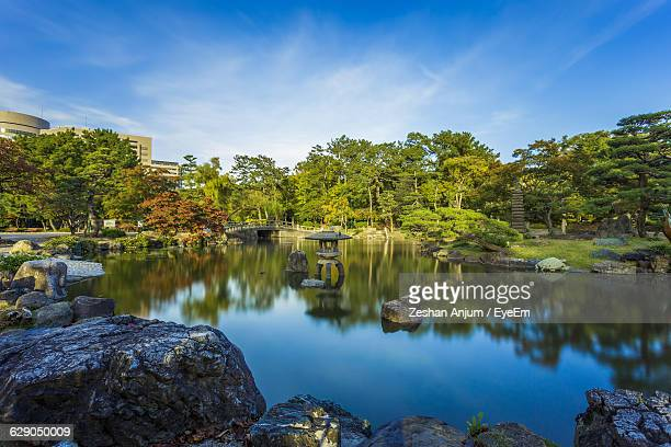 Pond With Trees Reflection In Tsuruma Park Against Sky