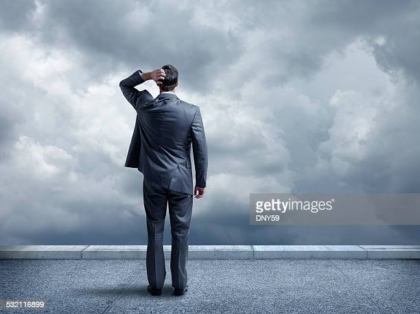 Pondering businessman looking out towards stormy sky
