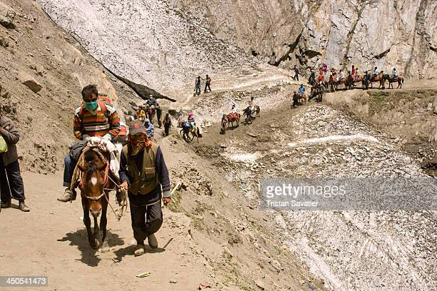Ponies and Hindu pilgrims on the trail to the Amarnath cave, crossing a area with old icy snow. Muslim Kashmiri pony-man provide transportation to...