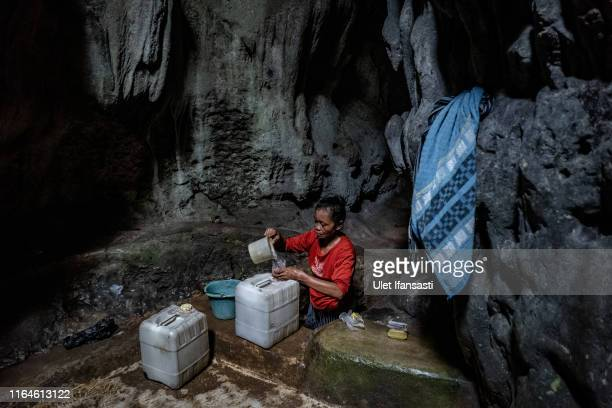 Poniyem fills a jerrycan full of water inside a cave at Klepu village Sawahan Kulon on August 28 2019 in Pacitan East Java province Indonesia During...